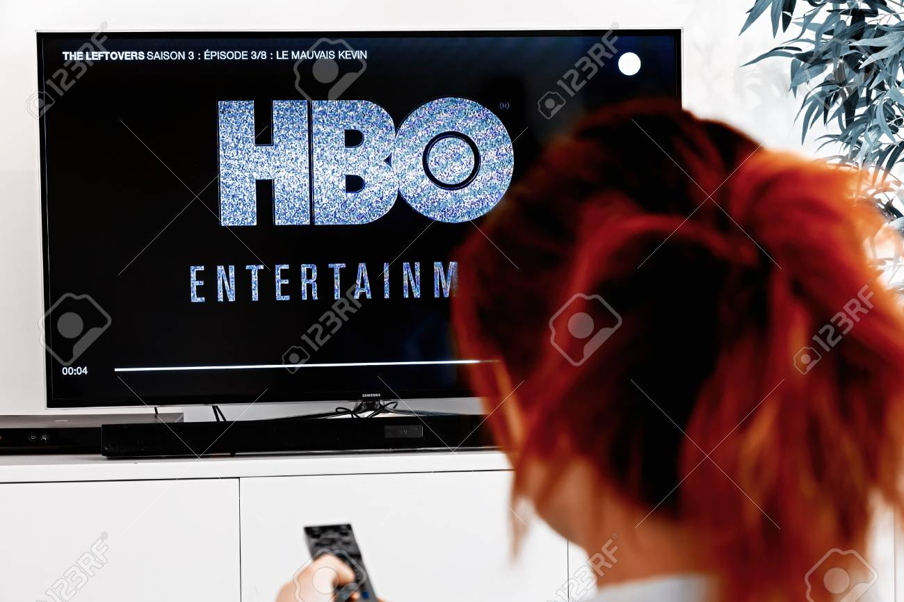 Benon, France - December 30, 2018: Woman watching tv serie produced by HBO which we see logo at the show begening. HBO is an American multinational entertainment company part of the WarnerMedia group - 115125609