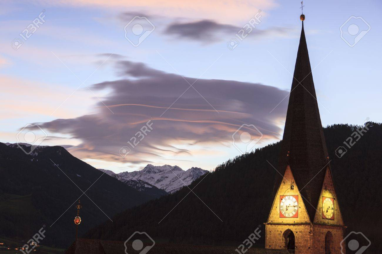 Lenticular cloud over the Alps with an illuminated church tower Stock Photo - 22133632