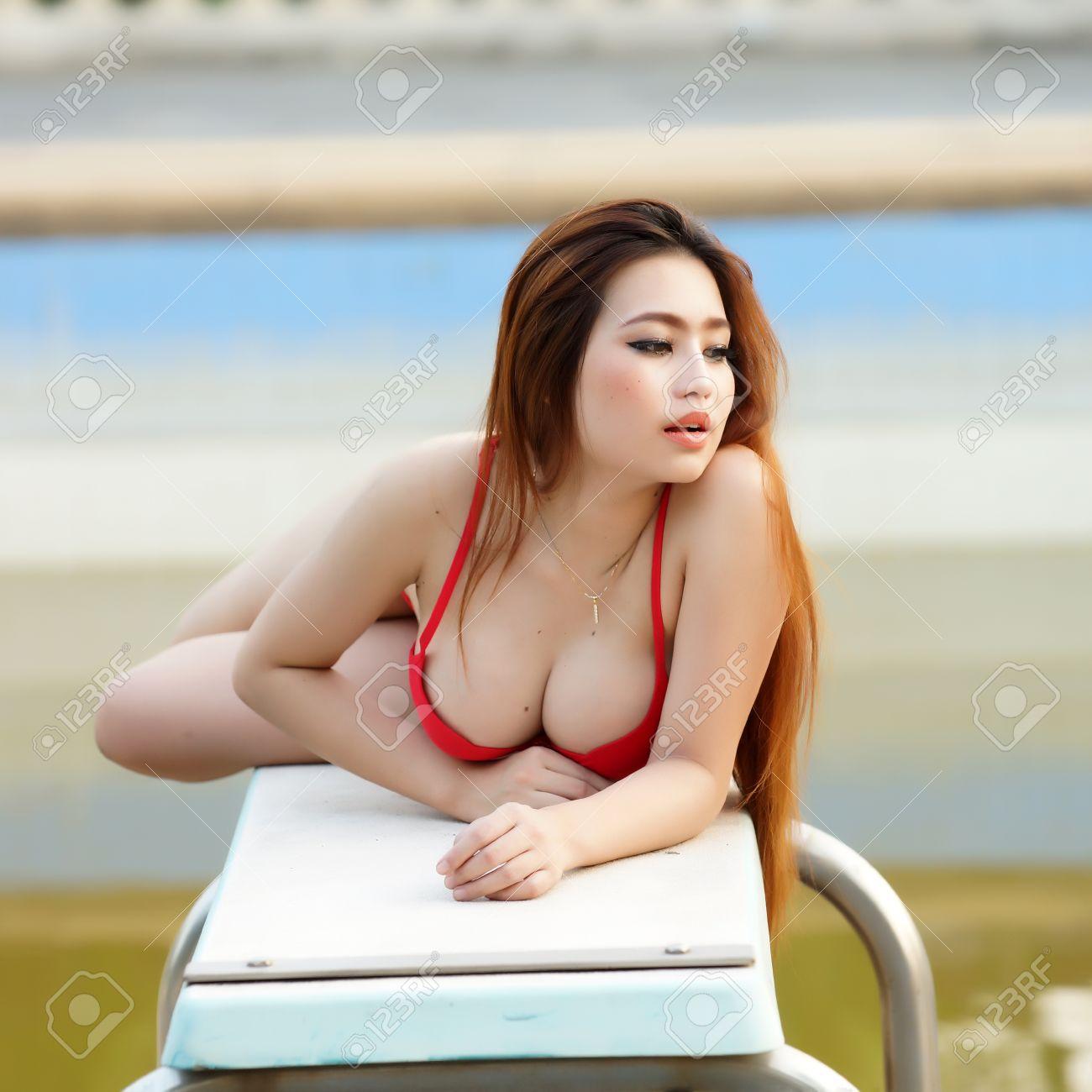 4c28c8291ad8 Foto de archivo - Hermosa mujer joven sentada en la piscina de la natación,  el modelo es la mujer asiática.