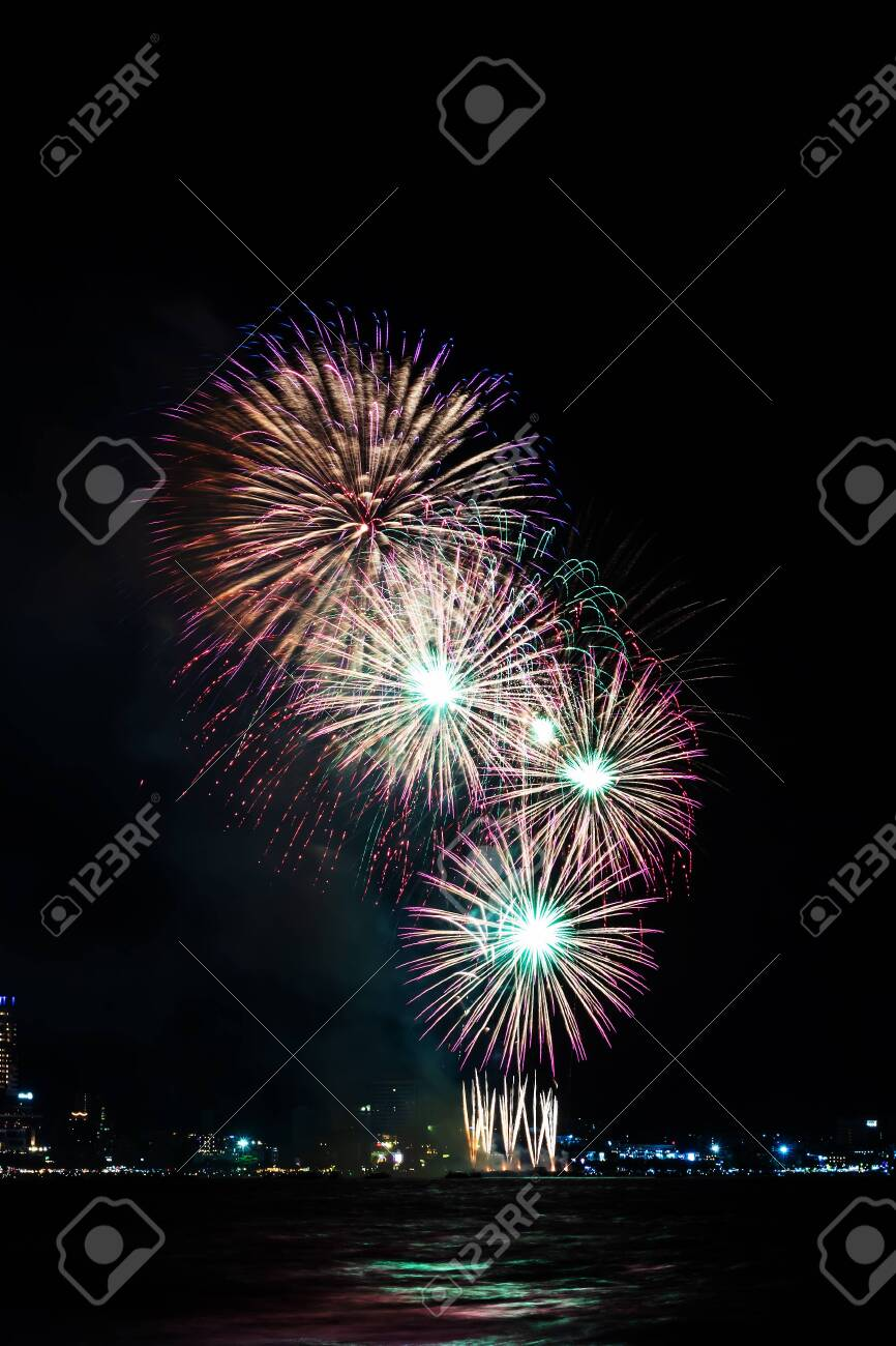 Fireworks over sea with city night on background. Festive colorful fireworks celebration in night sky. - 134072777