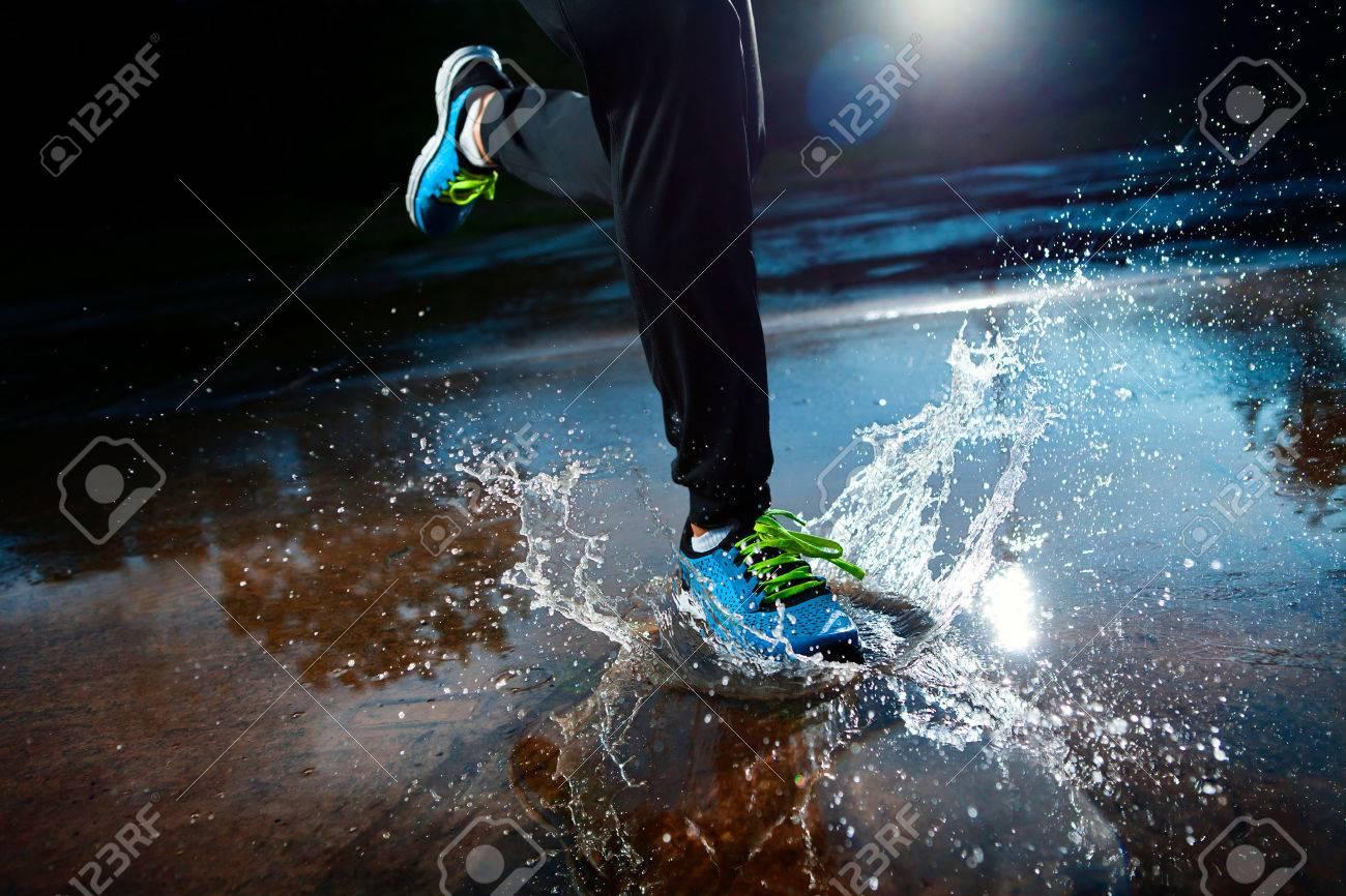 Single runner running in rain and making splash in puddle - 23684991