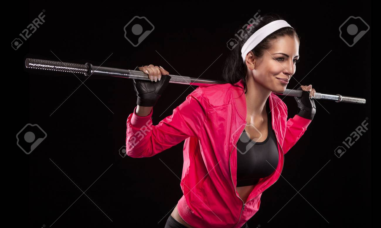 Beautiful young woman exercises with barbell dumbbell Isolated over black background (colored, retouched) Stock Photo - 25791940