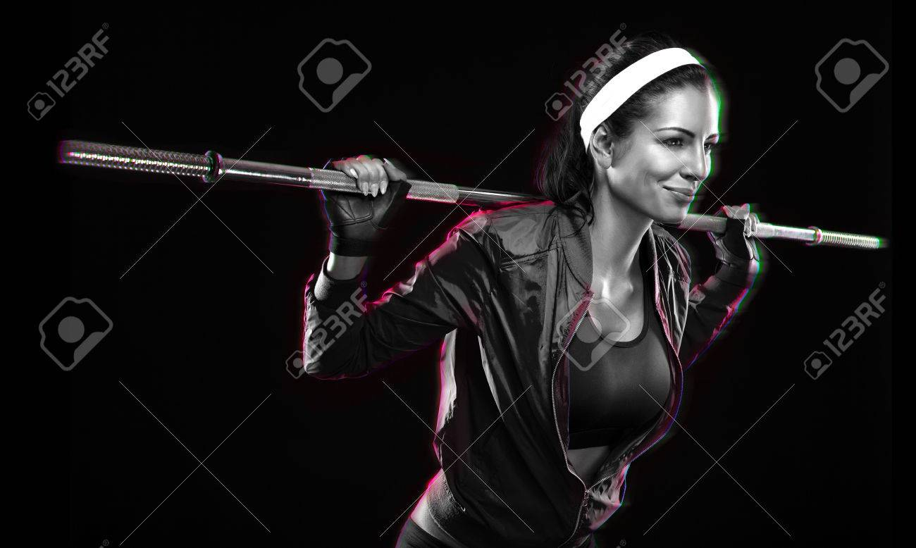 Beautiful young woman exercises with barbell dumbbell Isolated over black background (colored, retouched) Stock Photo - 25791945
