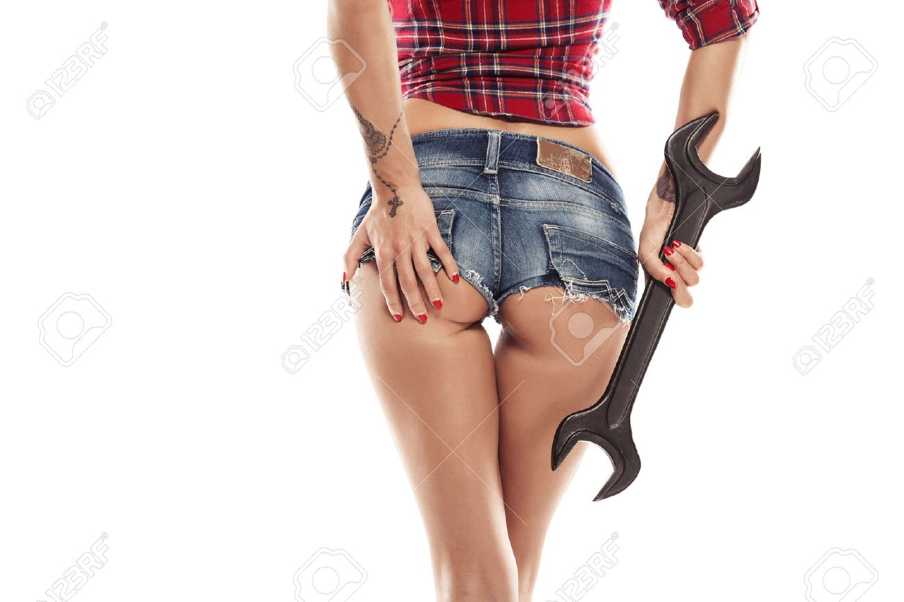Nice woman mechanic showing bum buttock and holding wrench isolated over white background - 38603606