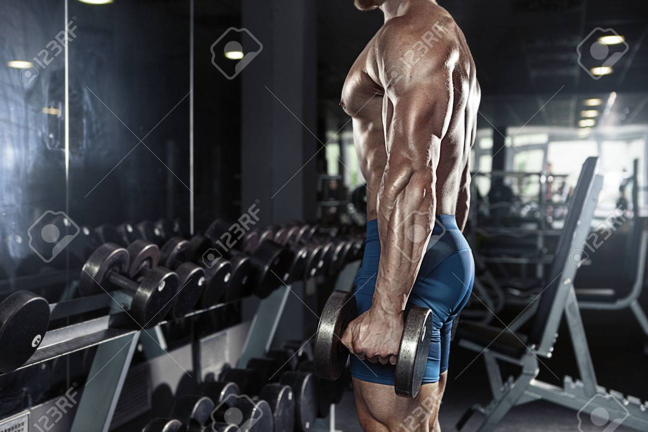 Muscular bodybuilder guy doing exercises with big dumbbell in gym - 41521334