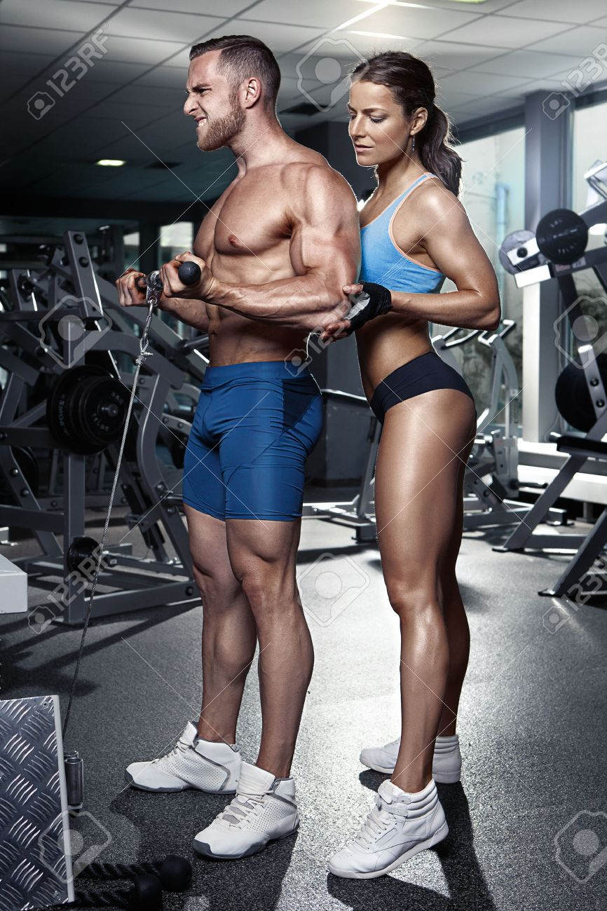 beautiful young sporty sexy couple doing biceps workout in gym Stock Photo - 41521336