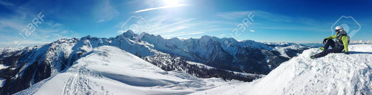 skier sitting on top of a mountain and relaxing, beautiful background blue sky - 52156712