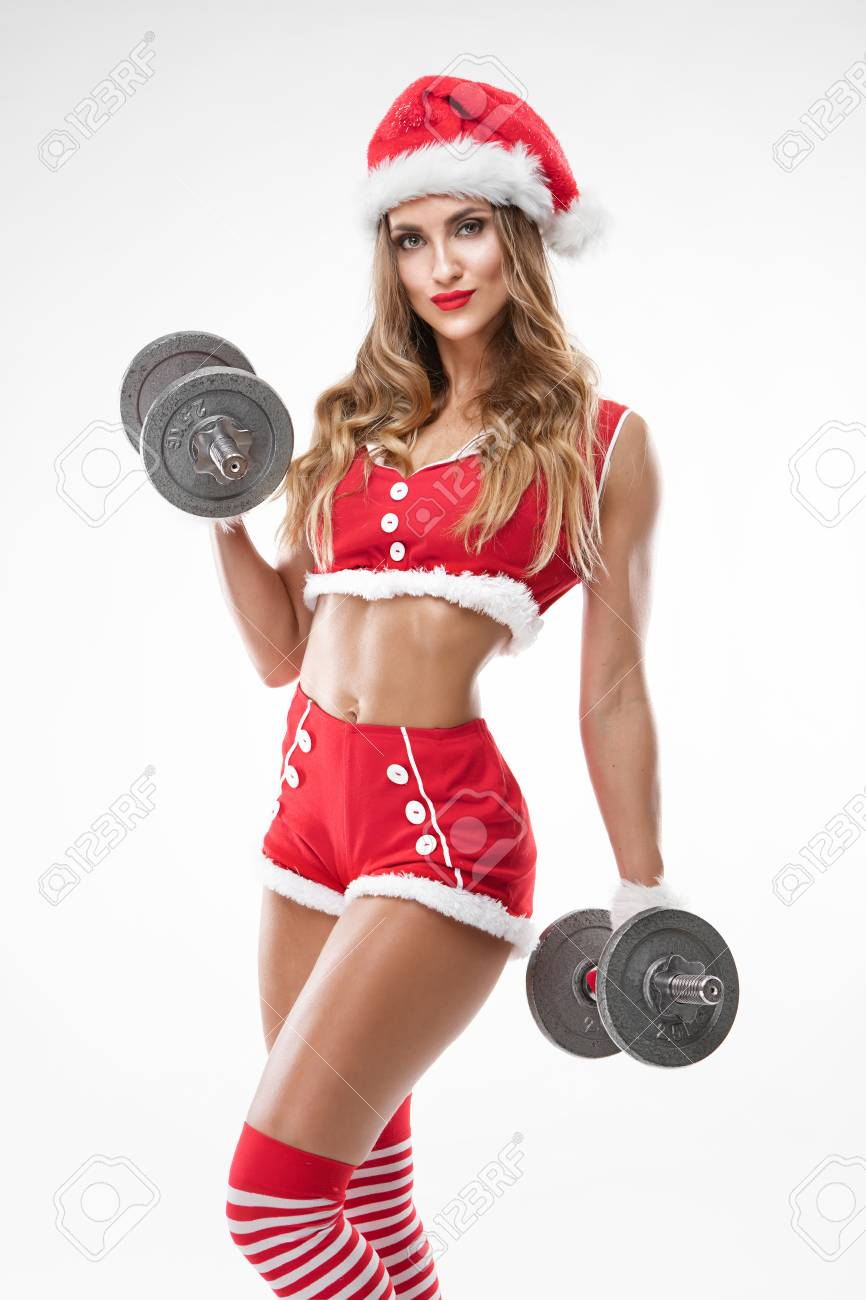 0a32b5759 beautiful sexy girl in santa claus clothes doing workout with dumbbell over  white background Stock Photo