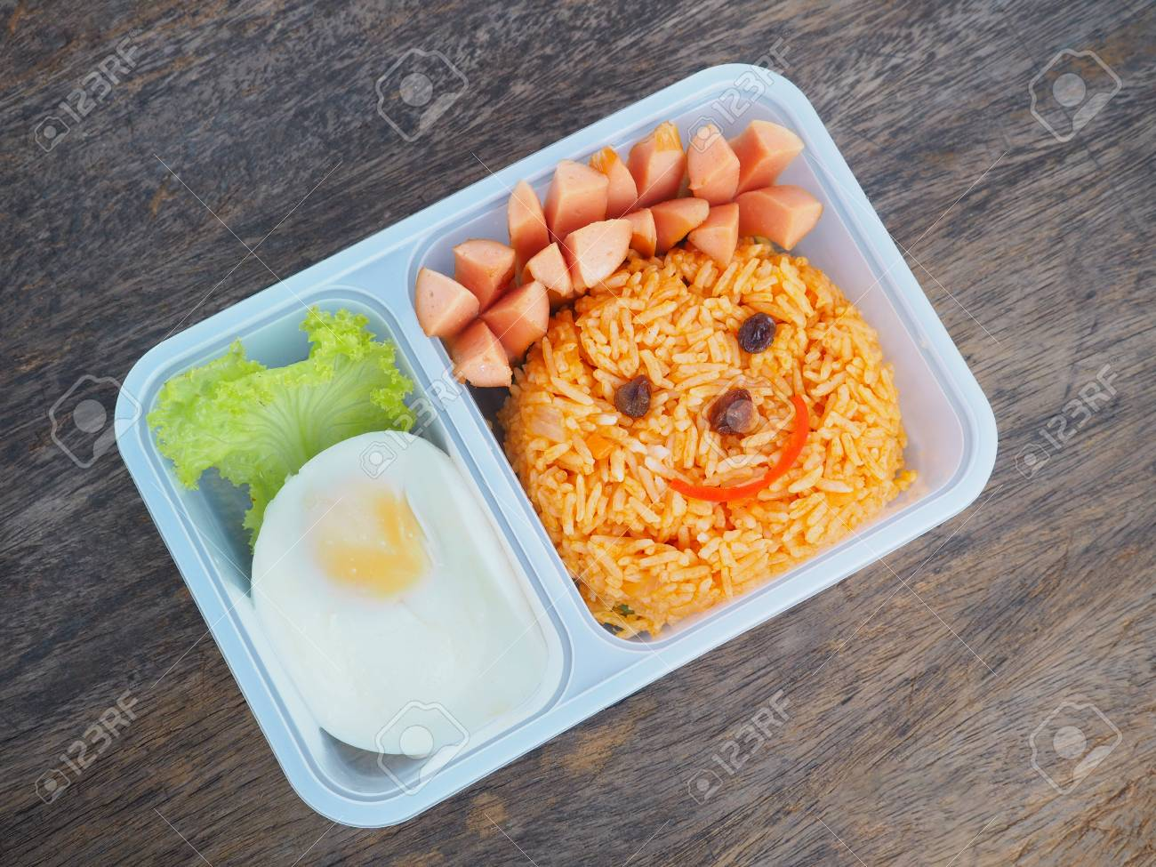 9d8803e42f Plastic school lunch box for kids with funny face of fried rice and egg on  wood