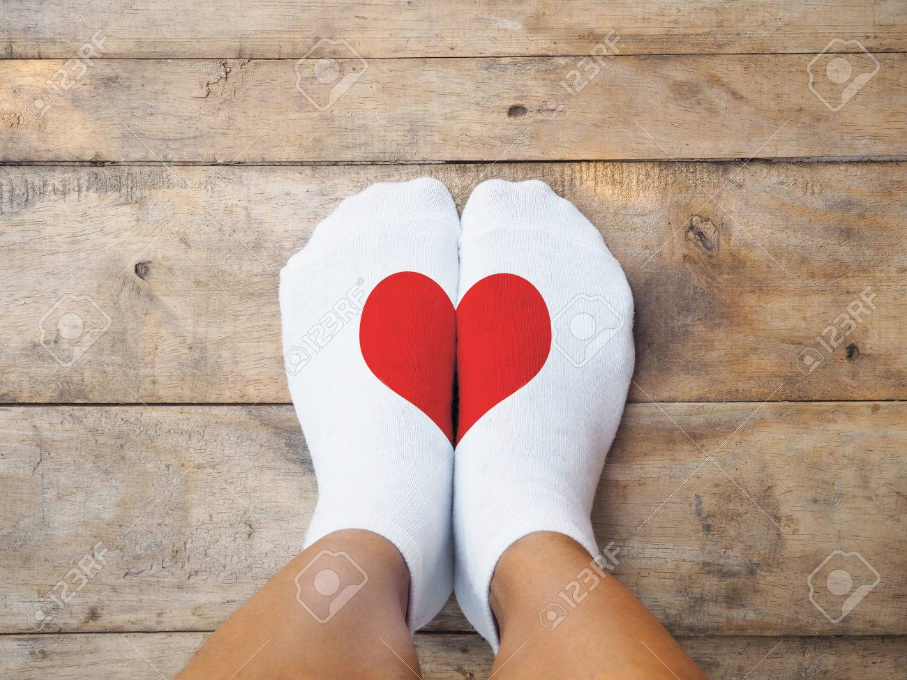 Selfie feet wearing white socks with red heart shape on wooden floor background. Love concept. - 69908797