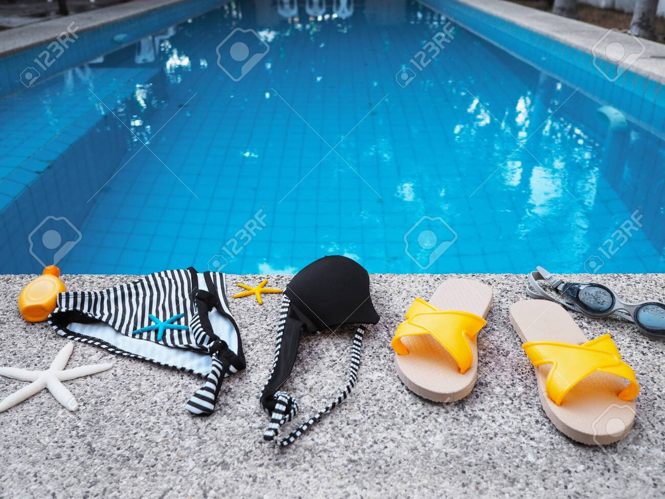 Woman swimming suit and accessories on edge of swimming pool...
