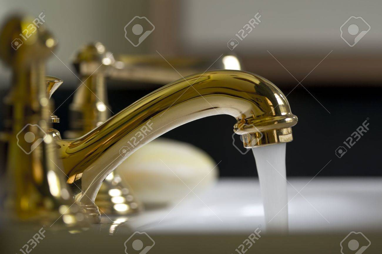 Water Running From A Gold Brass Bathroom Faucet Stock Photo - Gold brass bathroom fixtures