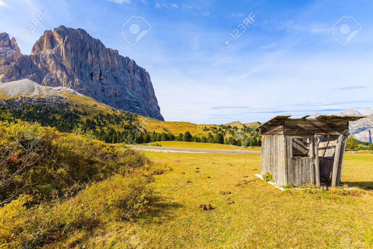 Small Wooden Hut On Meadow In Dolomites Mountains Near Passo Sassolungo,  Italy Stock Photo