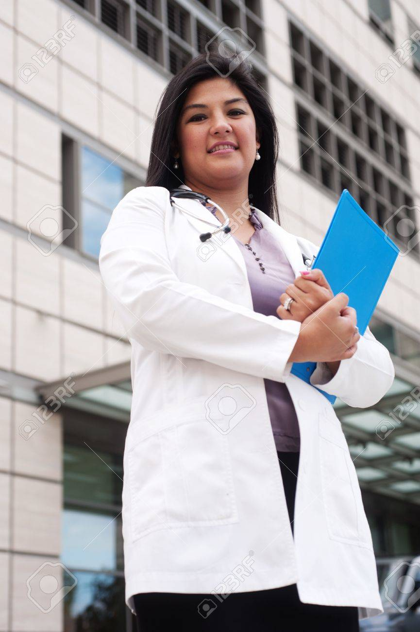 portrait of a young female doctor standing outside in front of a medical building holding a clipboard Stock Photo - 13138208