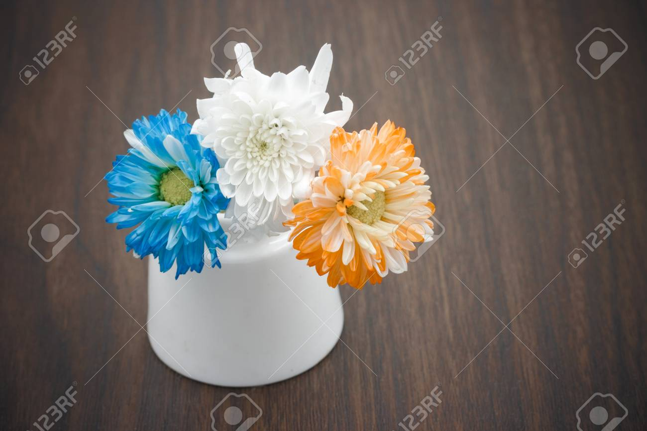 Blue White And Orange Flowers In Vase On Wooden Table Stock Photo