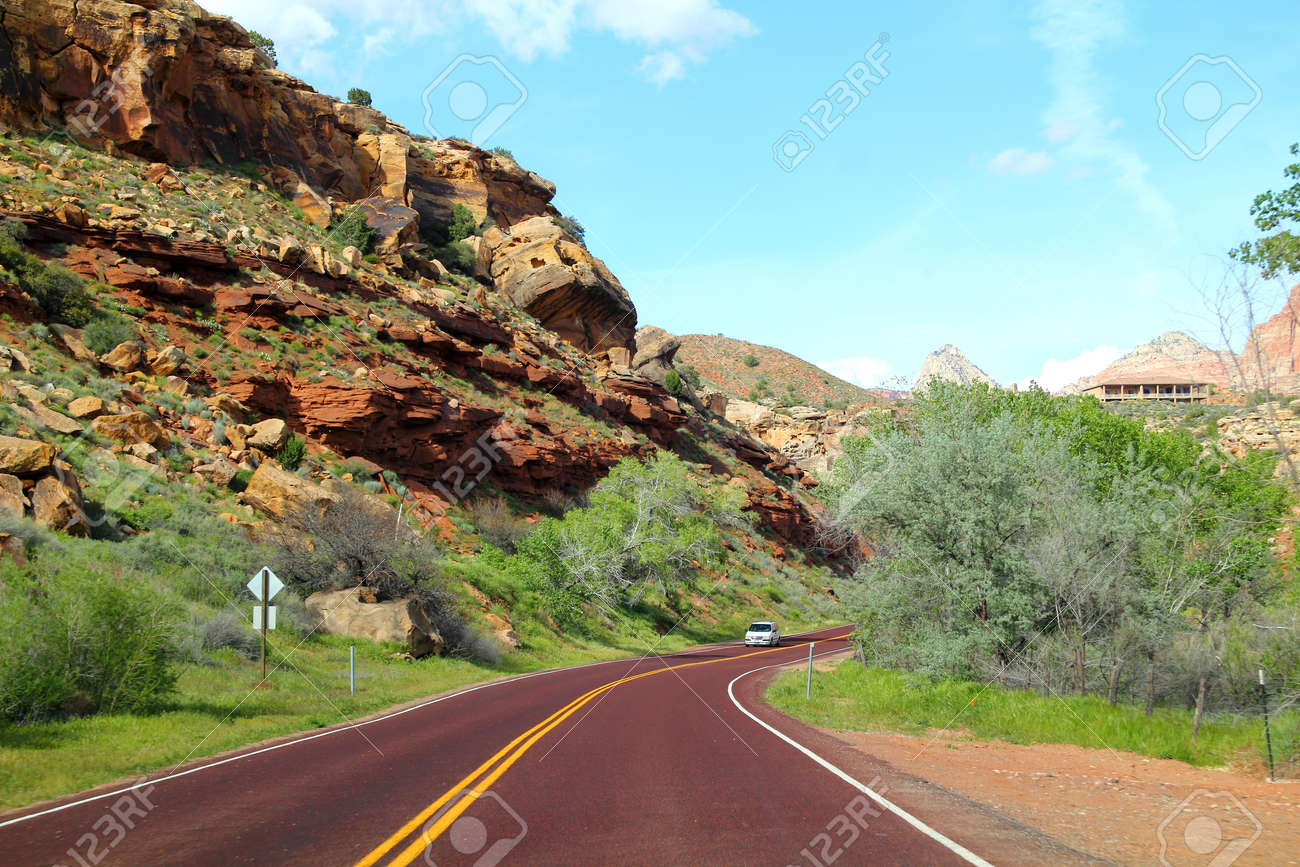 Road in USA with gras on the sides, hills in the background. - 16159838