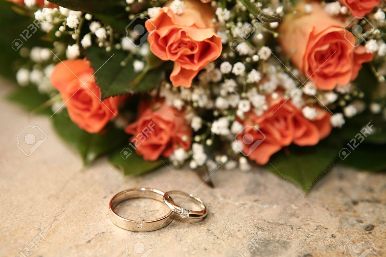 photo wedding rings and orange roses orange wedding rings Stock Photo Wedding rings and orange roses