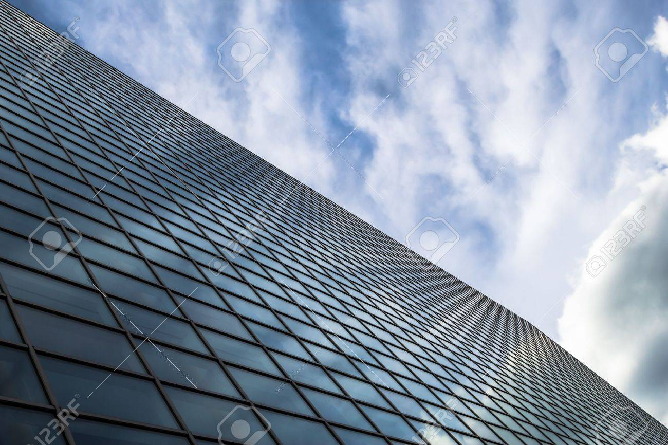 angled view of a glass wall of an office building infinity effect in the blue sky building an office