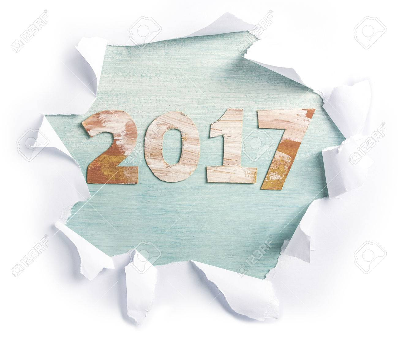 Photo of numbers forming '2017', cut out of paper with golden and white paint strokes, shot from above on light teal background, with torn paper on it. New Year greeting card or annual report design - 63701756