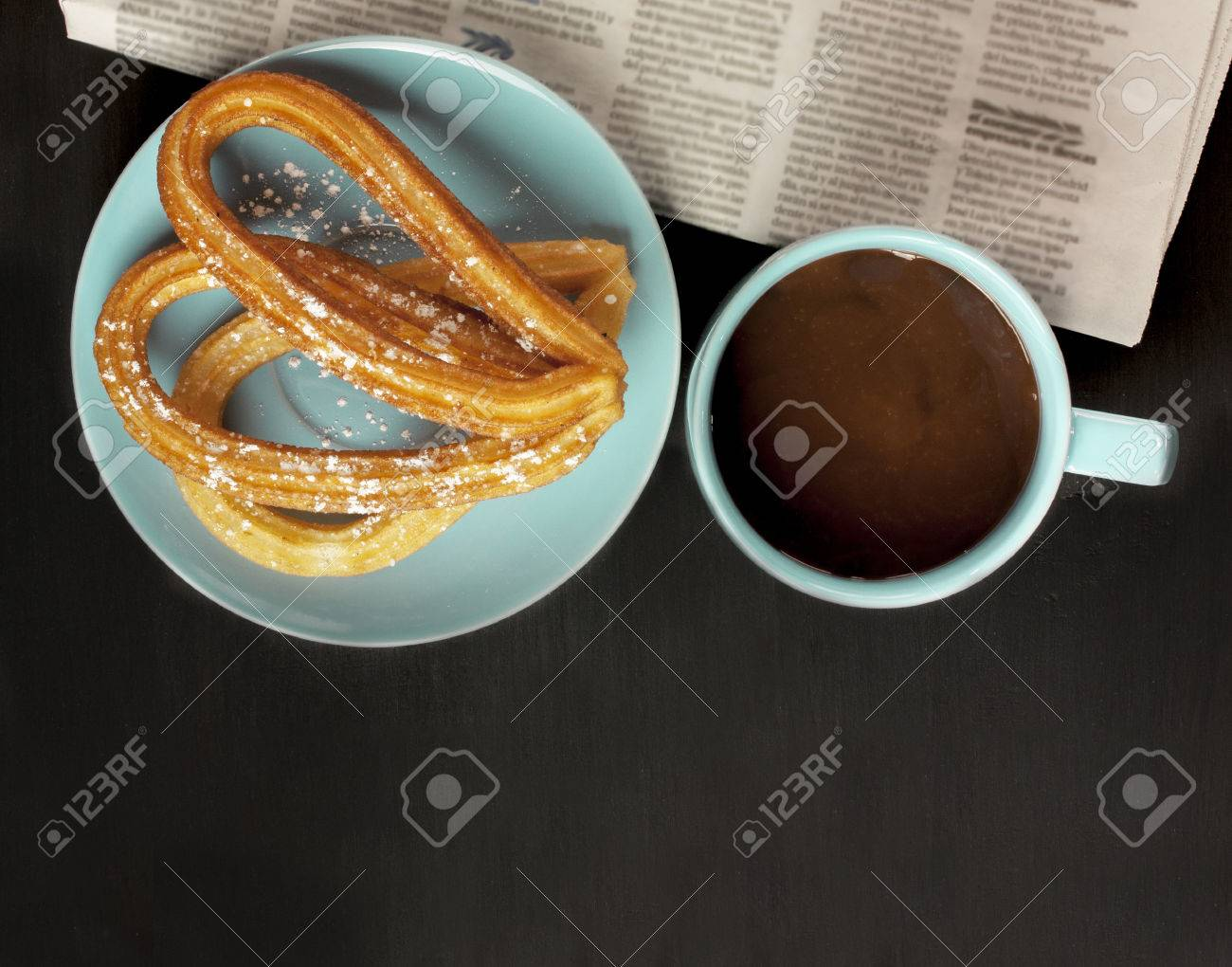 Plate of churros, traditional Spanish, especially Madrid, dessert, particularly for Sunday breakfast, with cup of hot chocolate, blurred newspaper, on dark wooden tabletop with copyspace - 66697756