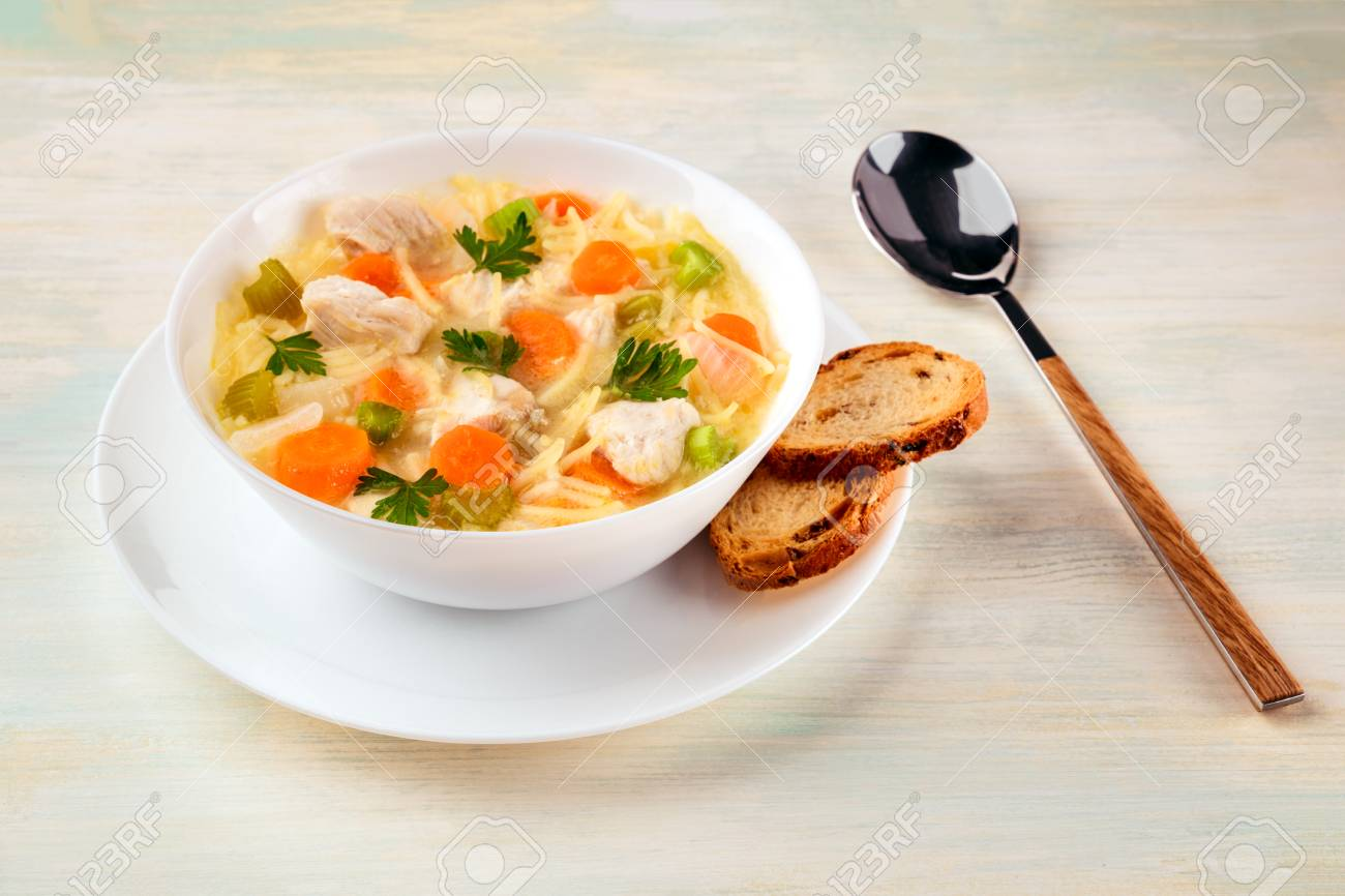 Chicken soup with noodles, bread, and copy space - 87647147