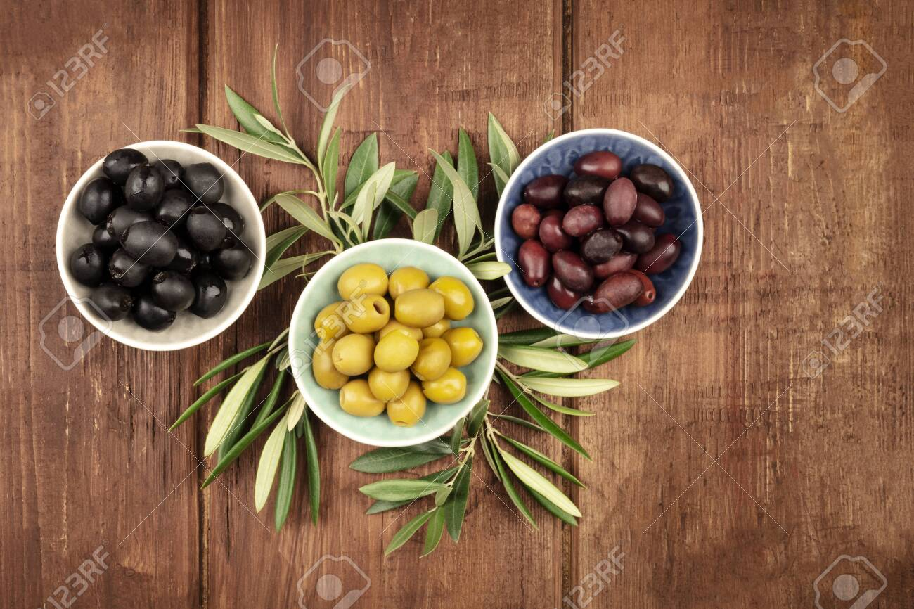 Various olives in bowls with leaves, shot from the top on a dark rustic wooden background with a place for text - 110610772