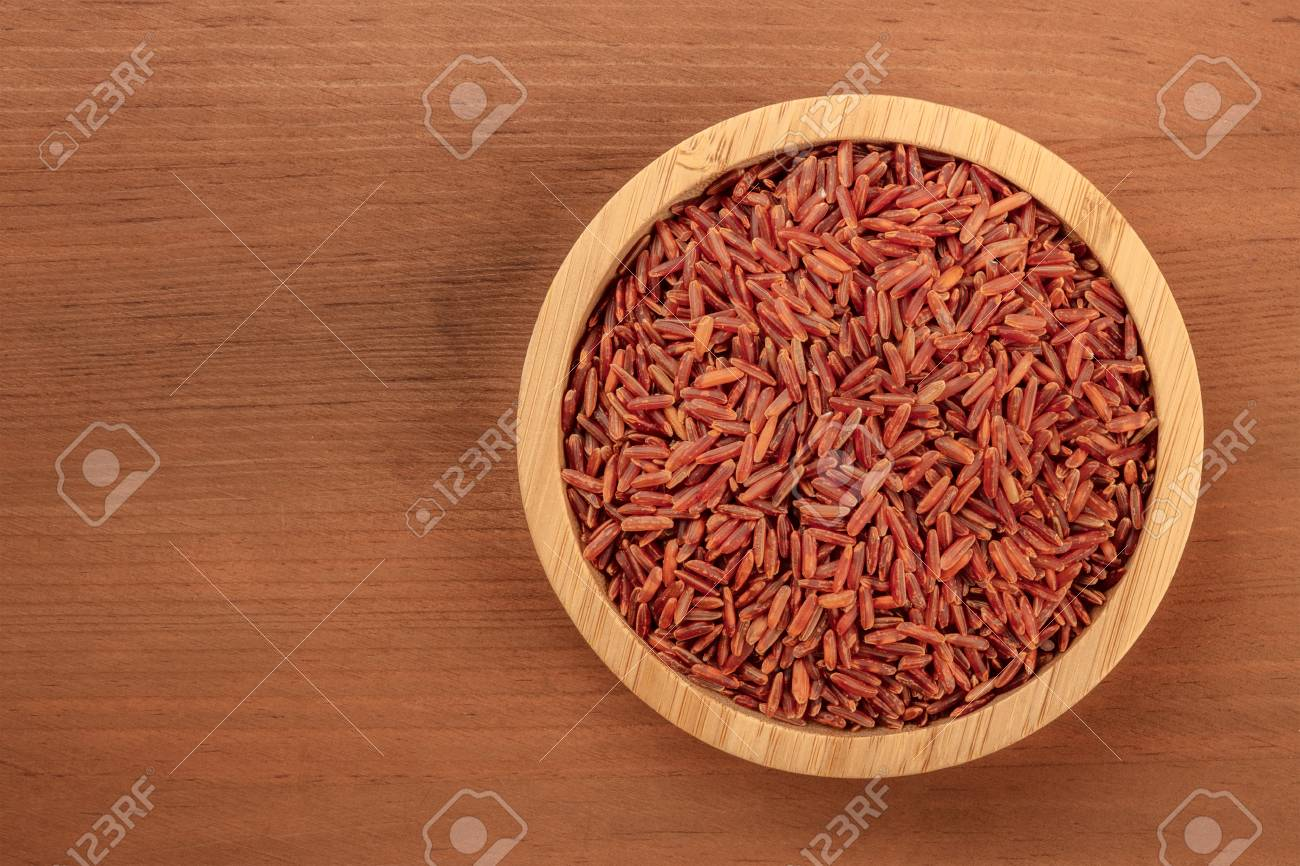 A photo of a long grain red rice, shot from above in a wooden bowl on a dark rustic background with copy space - 112158163