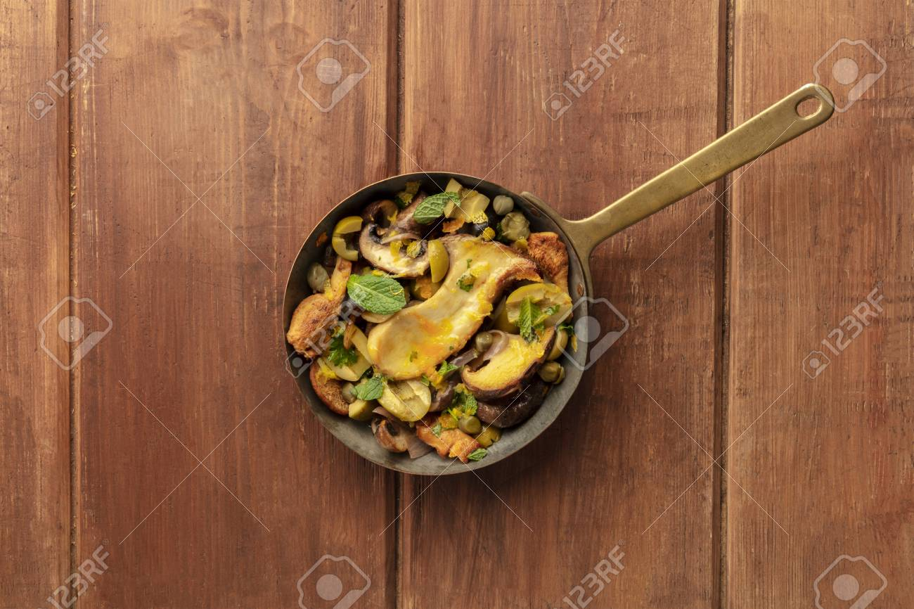 Rustic mushrooms and olives saute in a cast iron pan with mint,