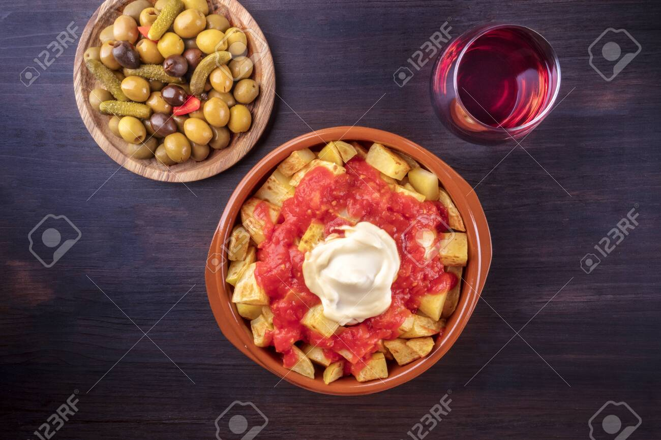 Patatas bravas, Spanish potatoes, with a glass of wine and olives, shot from the top on a dark background with a place for text - 130114809
