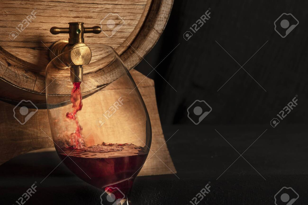 Pouring wine panoramic shot, a design template with copy space. A wine glass filled from an oak barrel, a closeup on a dark background with a place for text - 135940635