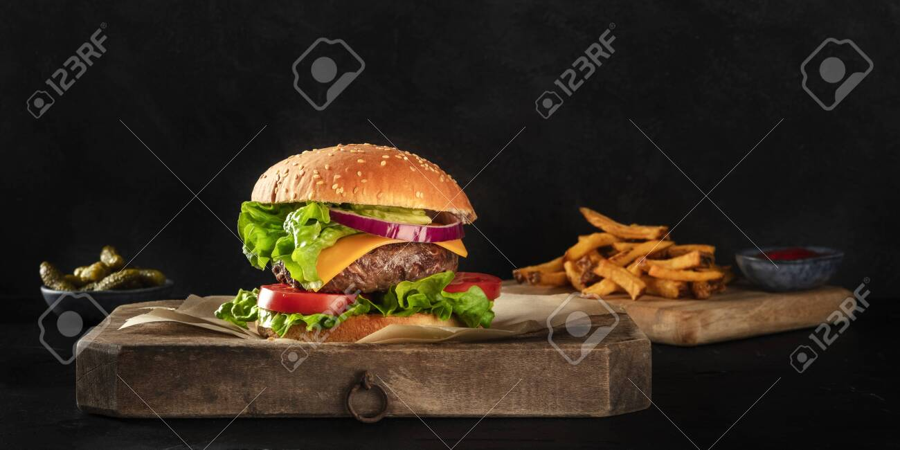 Burger with beef, cheese, onion, tomato, and green salad, a side view panorama on a dark background with French fries and pickles, with copy space - 142430265