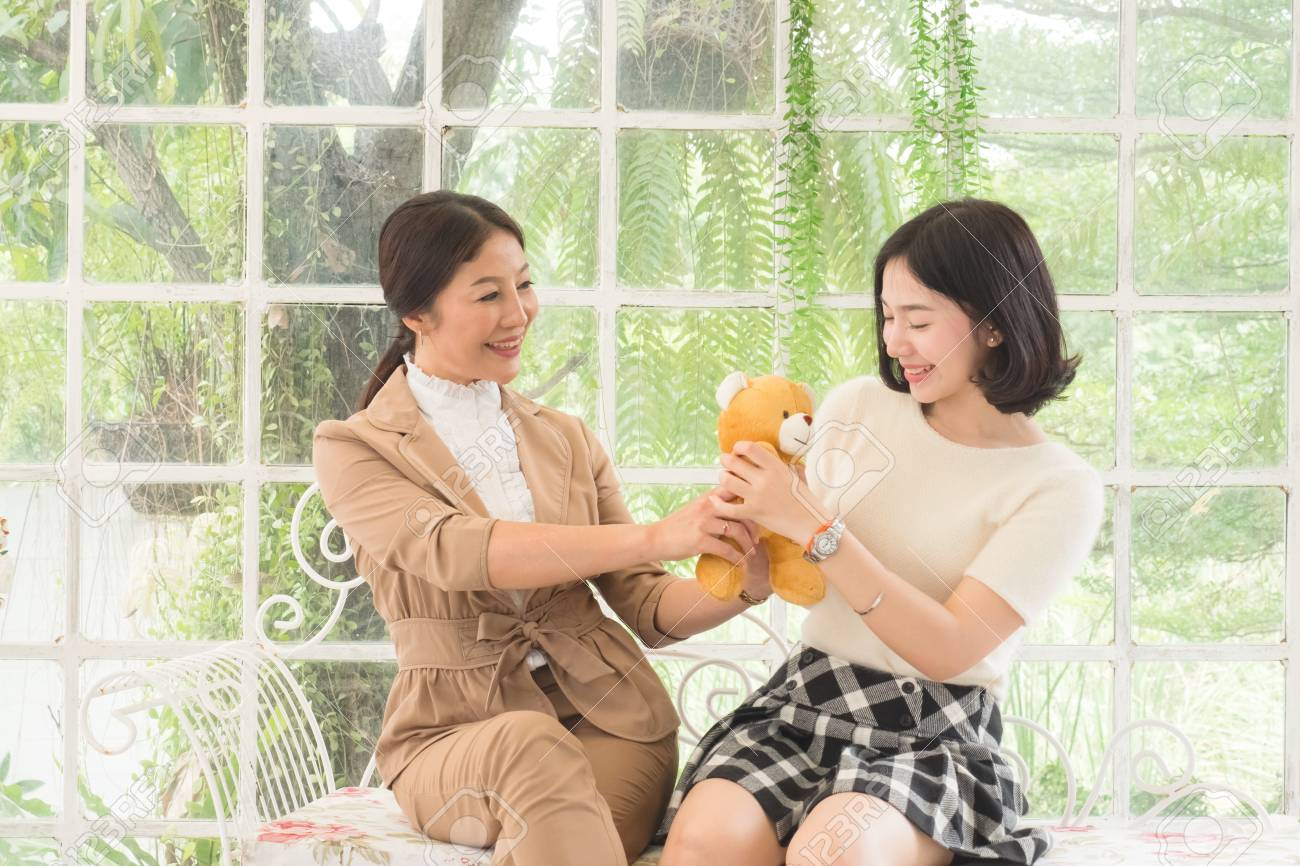 Mother Giving Birthday Present To Teen Daughter Concept Family Stock Photo