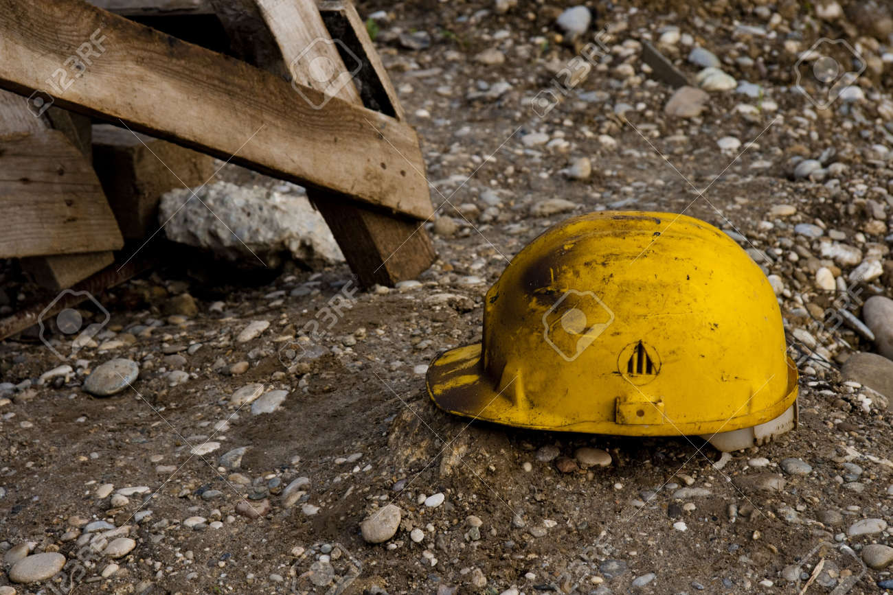 Dirty old work helmet left on the ground of construction site Stock Photo - 7949434