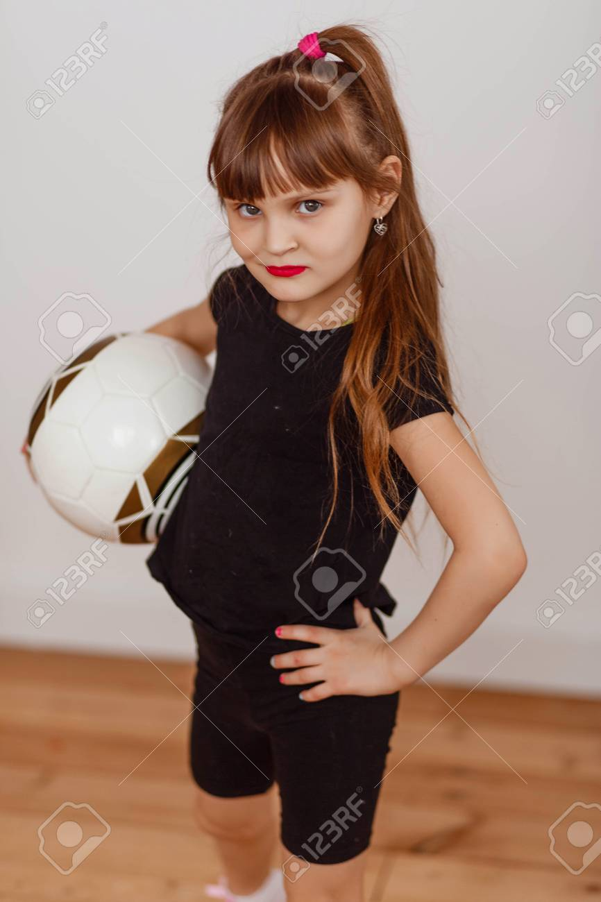 6104681ff little girl in black uniform with a soccer ball at the white wall Stock  Photo -