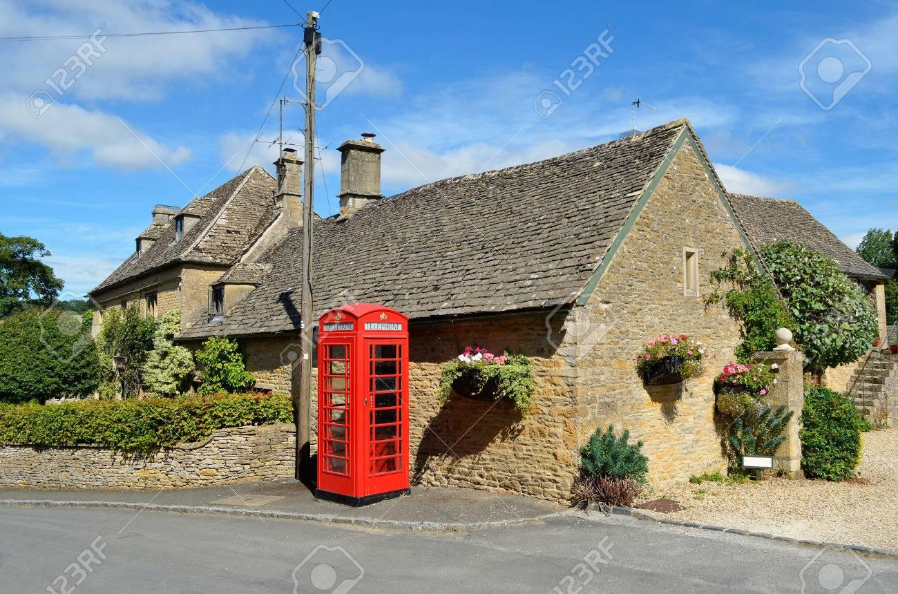 color miel casas de piedra y una caja de telfono rojo en un pueblo de los
