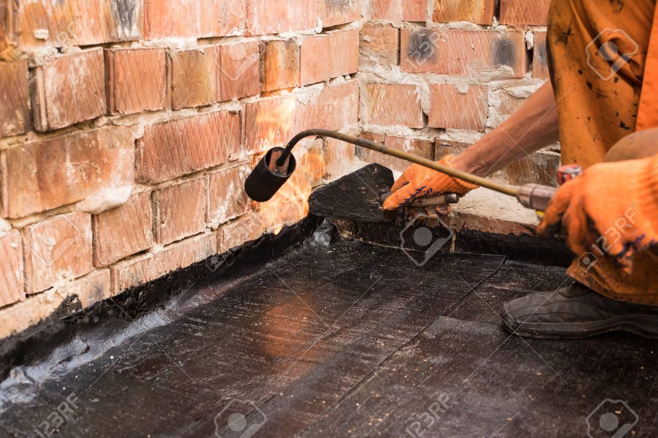 Flat roof installation  Heating and melting bitumen roofing felt