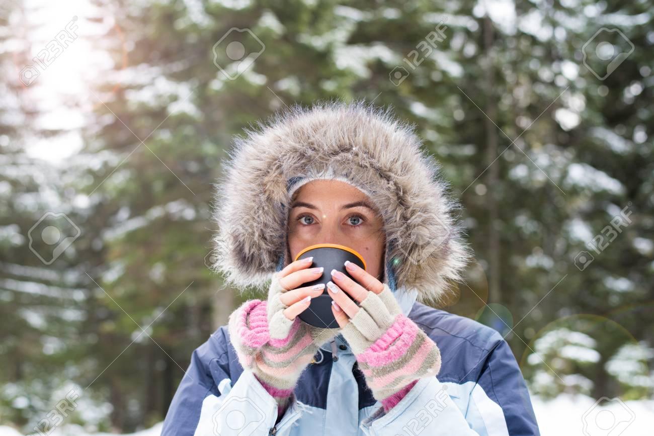 a1c10d494c89 Ragazza che beve il tè caldo nel ritratto foresta di inverno. Una giovane  ragazza in abiti invernali caldo con una tazza con una bevanda sullo sfondo  del ...