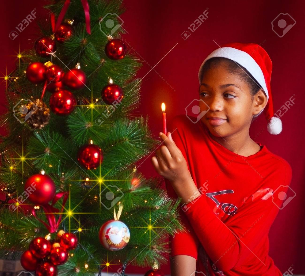 bbafecf77e Chica negro vestido como Santa Claus que decorar el árbol de Navidad con  luces