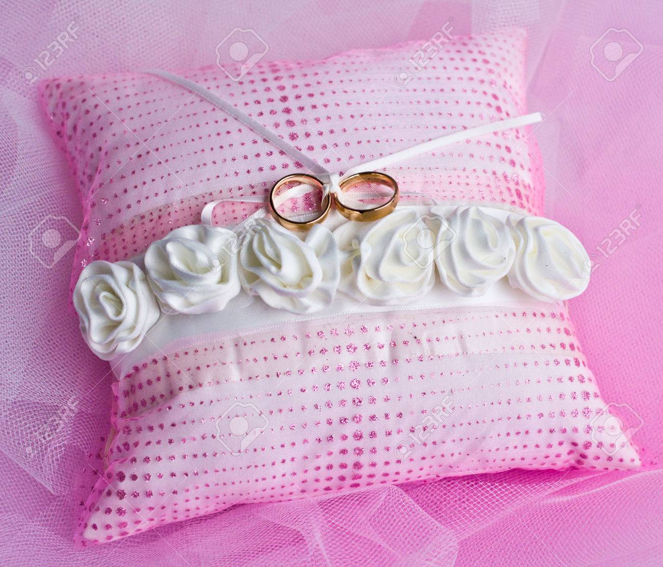 Double Gold Rings Tied On A Pink Pillow With White Roses Stock Photo ...