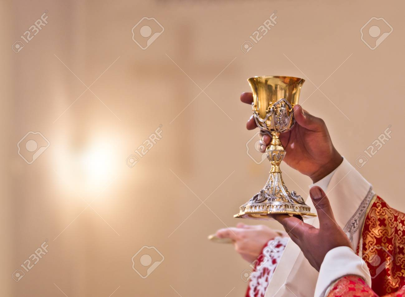 hands of the priest raise the cup containing the blood of Christ, the sacred grail - 97952379