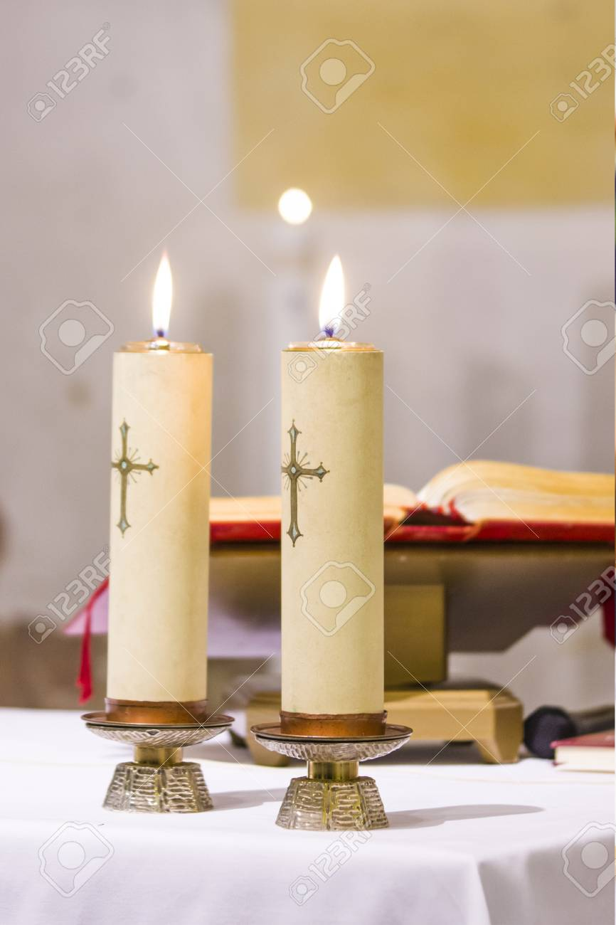 two candles with a cross light illuminate the church's atre with the blessed gospel, water and wine ready for holy mass - 107505198