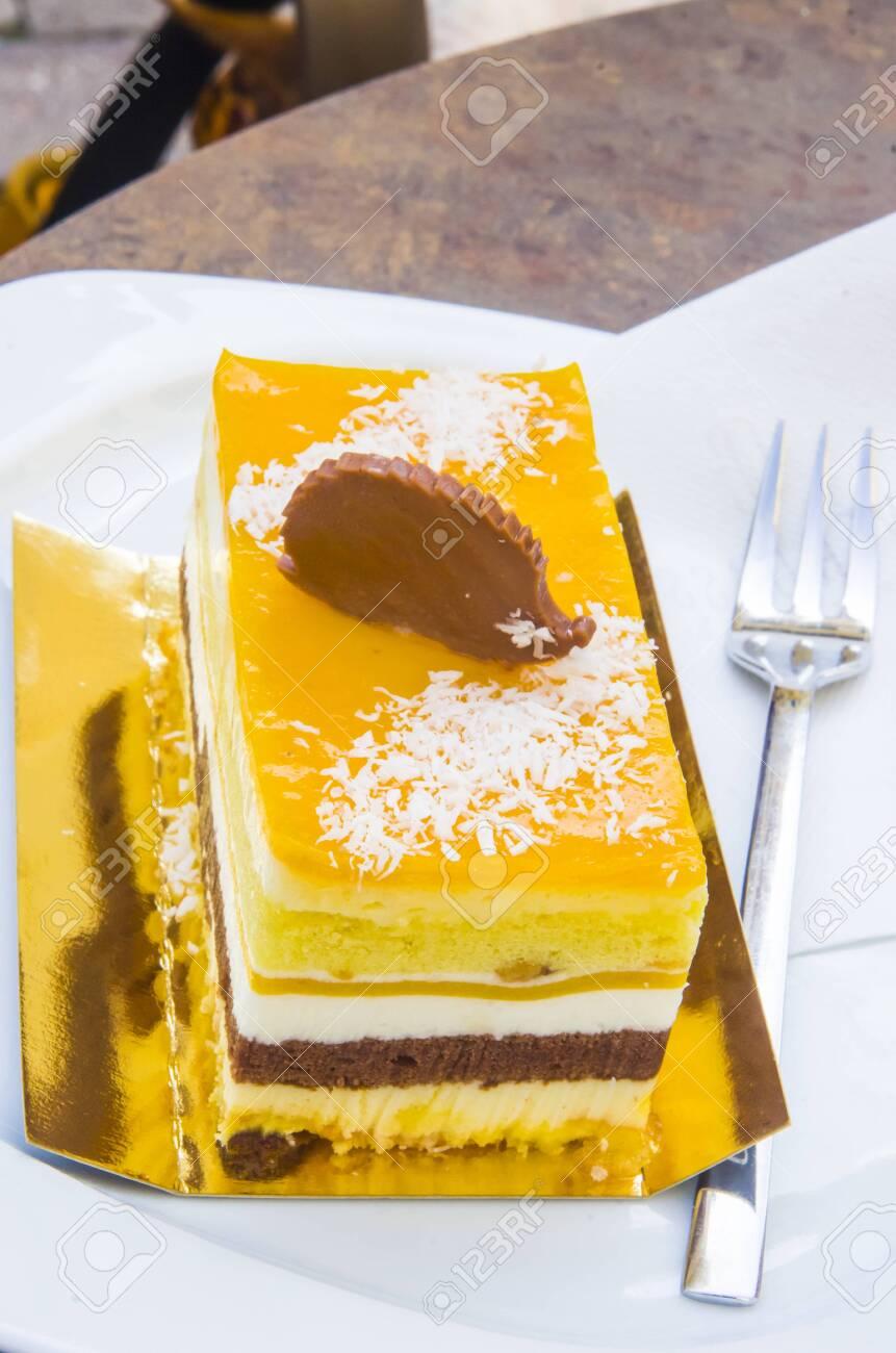 chocolate parfait, sponge cake, cream and mango with a milk chocolate hedgehog decoration - 145781624
