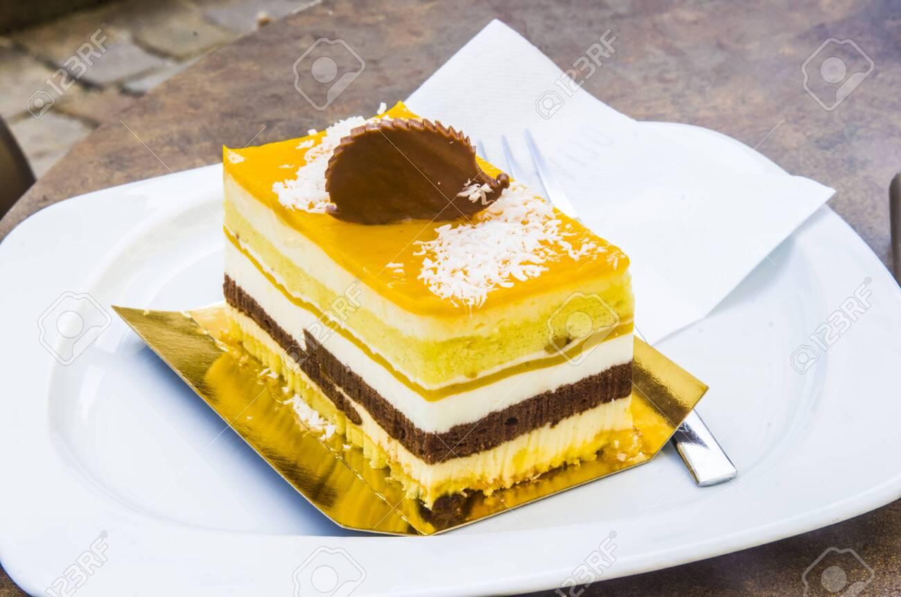 chocolate parfait, sponge cake, cream and mango with a milk chocolate hedgehog decoration - 145782235