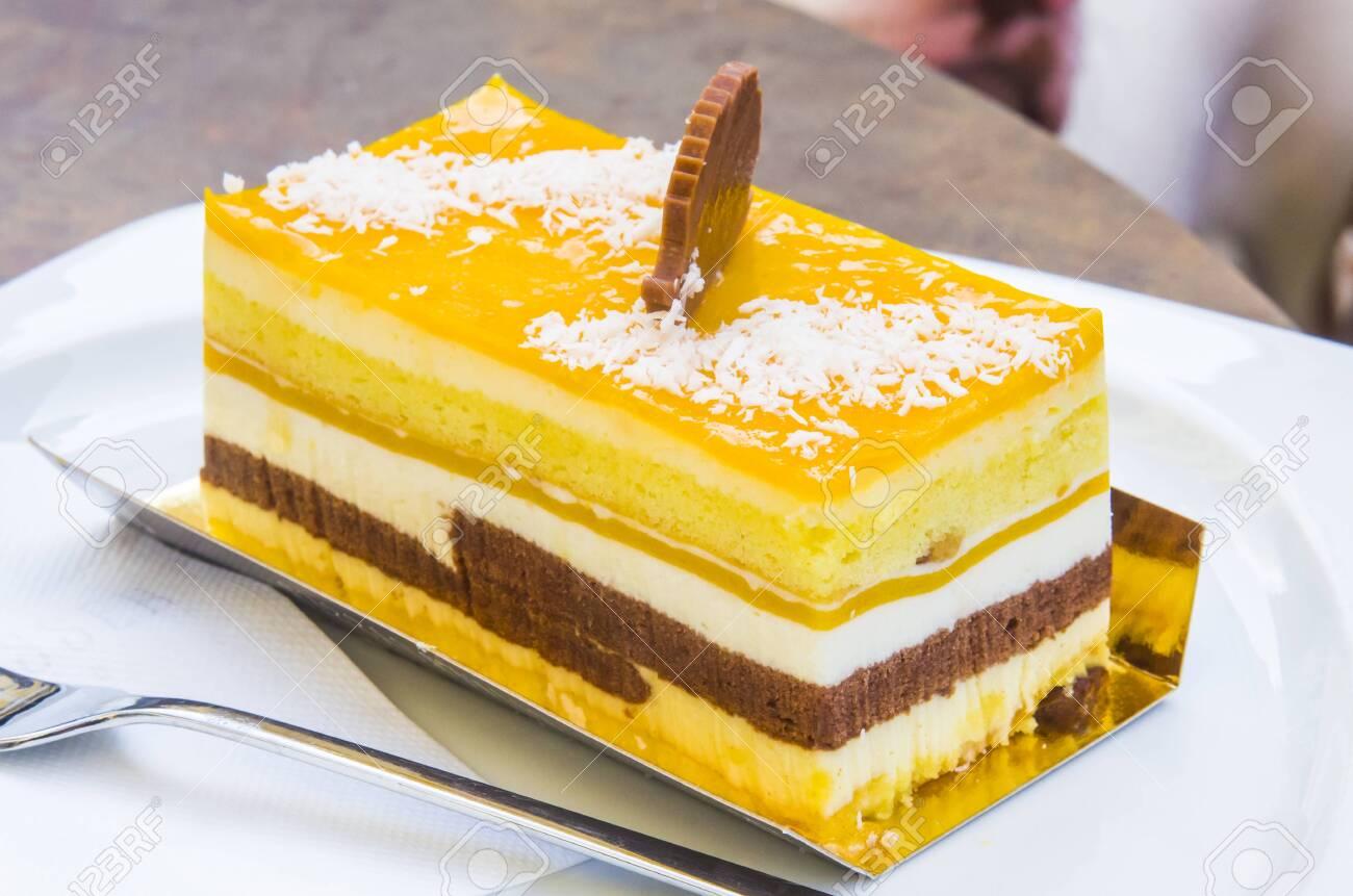 chocolate parfait, sponge cake, cream and mango with a milk chocolate hedgehog decoration - 145782238