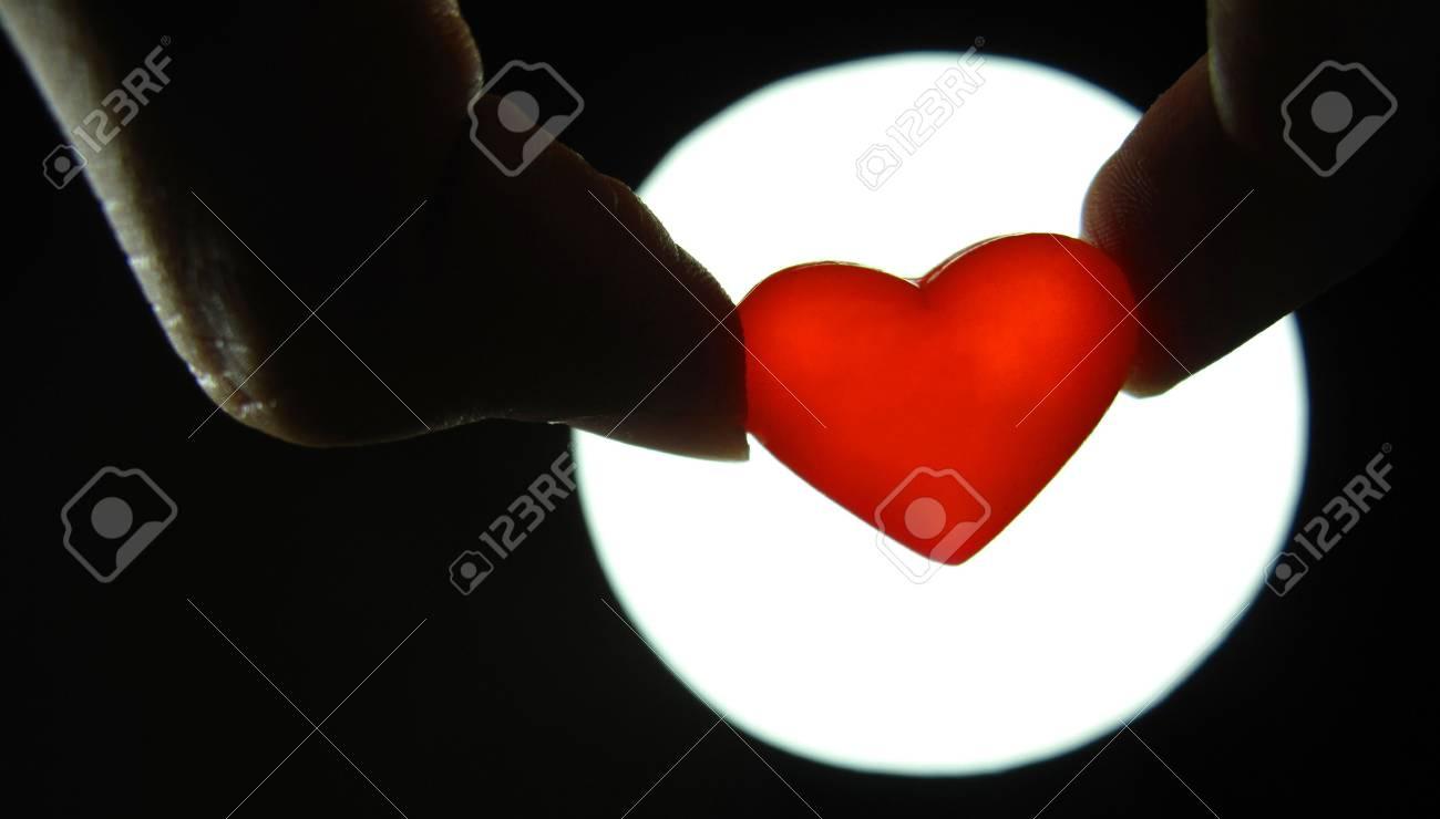 finger holding heart background Stock Photo - 13326303
