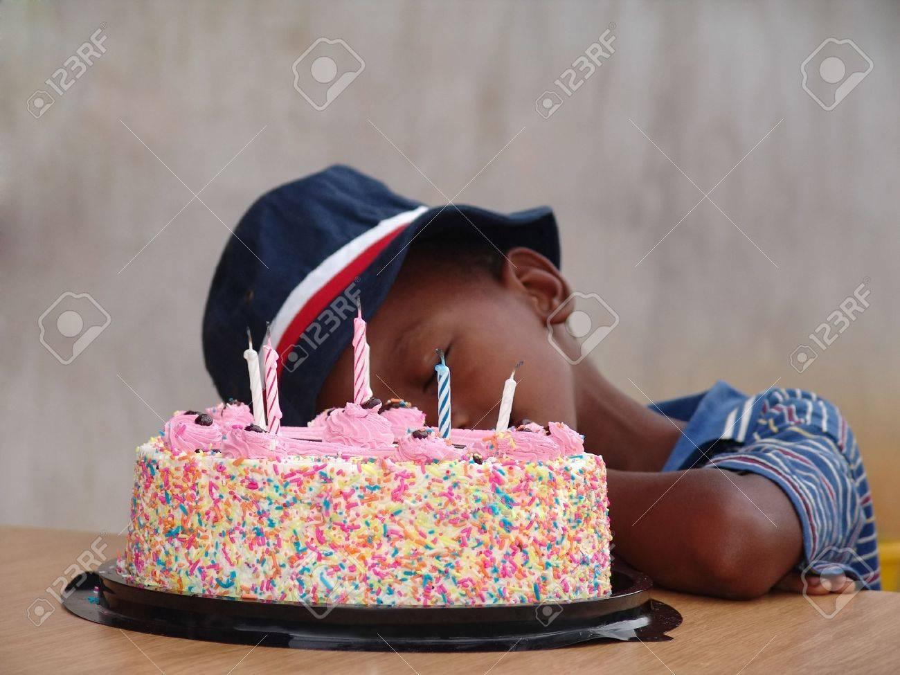 Birthday Boy Sleeping Next To Multicolor Cake Stock Photo