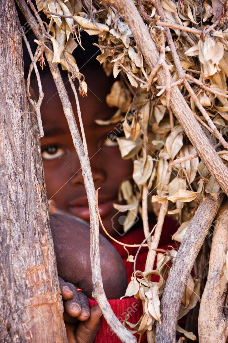 Village child hiding between the branches of an african hut front focus Stock Photo - 4118558