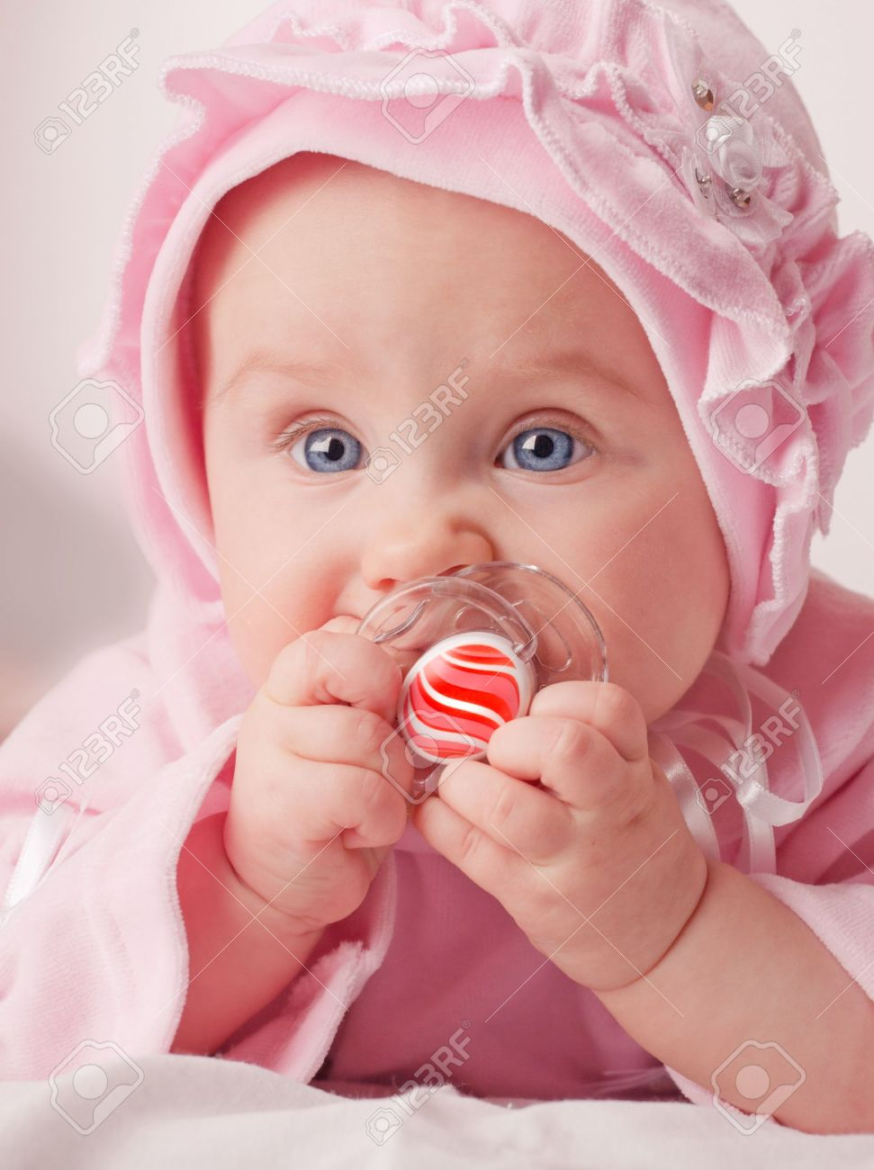 small cute baby holding a red dummy stock photo, picture and royalty