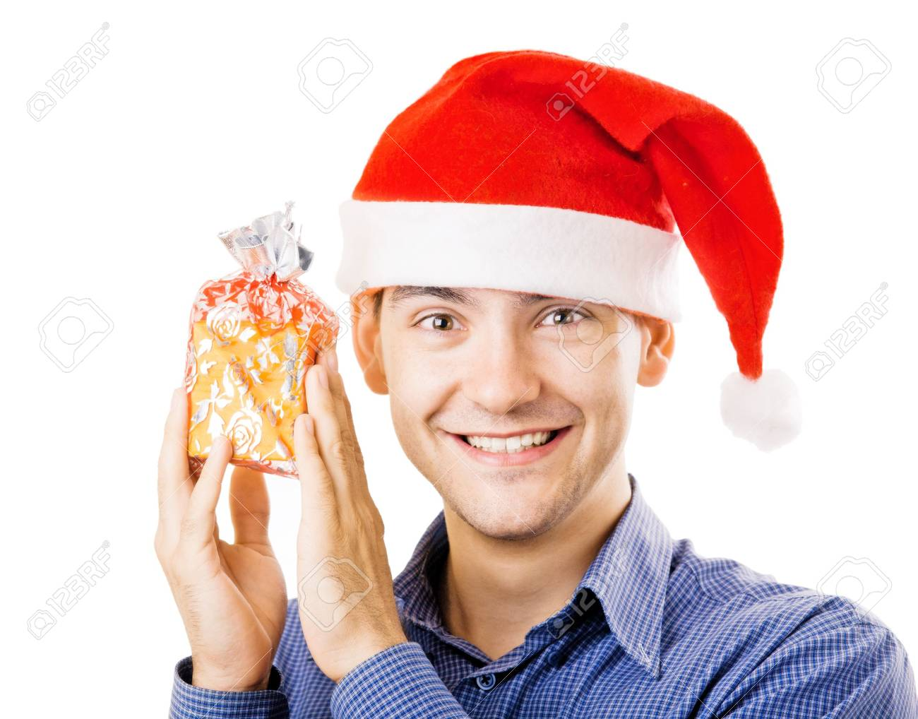 Young man in santa hat holding a present Stock Photo - 5646471
