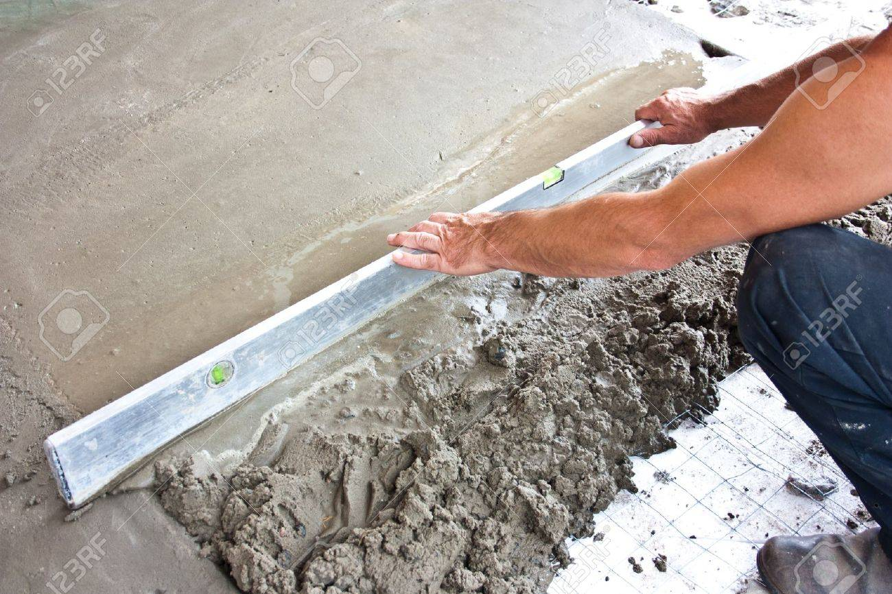 Plasterer concrete worker at floor work of  construction site Stock Photo - 16987017